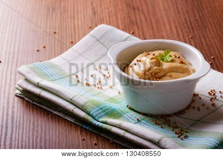 Bowl With Mustard And Seeds On Green Cloth And Wooden Board