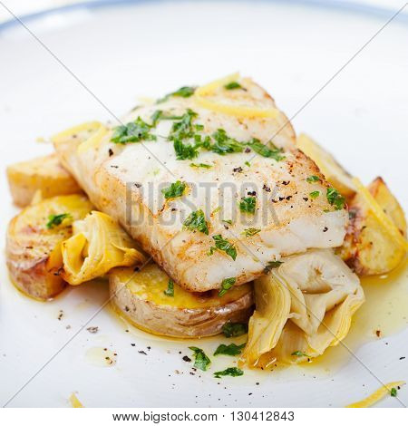 Roasted cod, codfish with baked potatoes and artichokes with lemon and herbs sauce on a white background