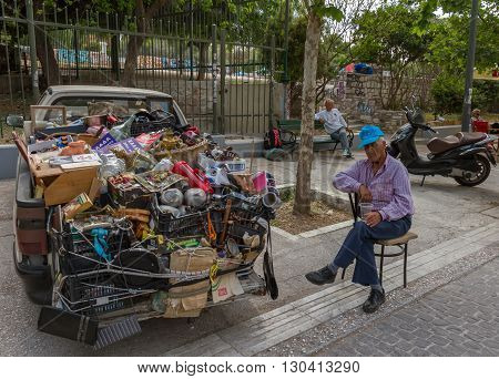 Athens Greece - April 30 2016: A half-asleep old person next to a van full of old stuff near the Ancient Agora Athens Greece