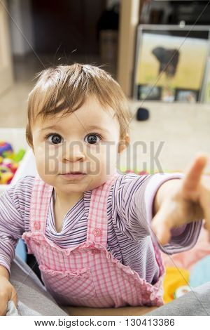 Baby Pointing At Camera With Wide-open Eyes