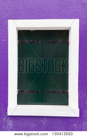 Picturesque old window with dark shutters on violet wall (Burano island Venice Italy)