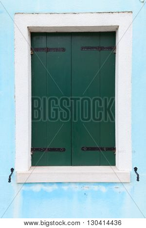 Picturesque old window with dark green shutters on light blue wall (Burano island Venice Italy)