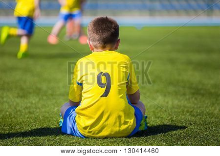 Young Boy Wearing Sport Outfit. Youth Soccer Player sitting on sports venue and watching soccer game.