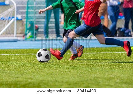 players playing football soccer game. Running players in grenn and red outfit sports uniforms