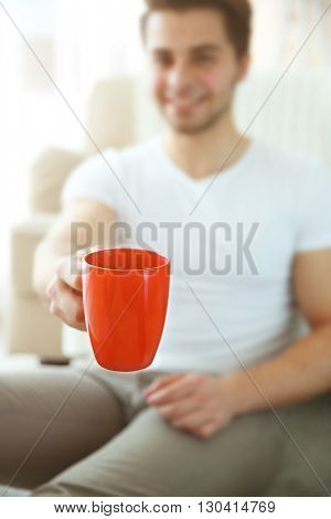 Portrait of young smiling man with red cup of coffee, unfocused. Focus on cup  of coffee