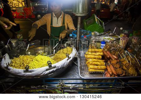 BANGKOK, THAILAND - FEBRUARY 13, 2016: Unidentified woman selling food on the street in Bangkok. Street food is a quintessential part of the Bangkok experience.