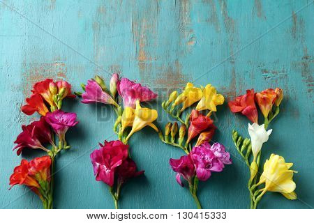 Beautiful freesia flowers on wooden background