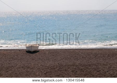Boat on Black volcanic beach at Kamari Santorini Greece