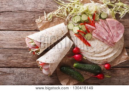 Tortilla Roll With Ham And Vegetables Close-up And Ingredients. Horizontal Top View