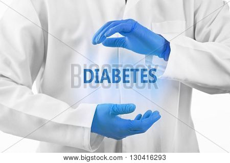 Doctor hands in medical gloves and text diabetes on white background