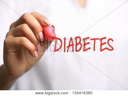 Young female doctor with pink marker and text diabetes