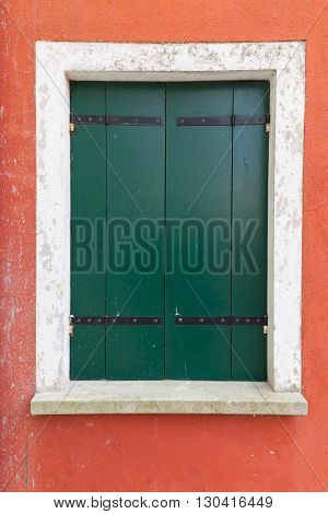 Picturesque old window with green shutters on red wall (Burano island Venice Italy)