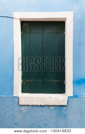 Picturesque old window with dark shutters on light blue wall (Burano island Venice Italy)