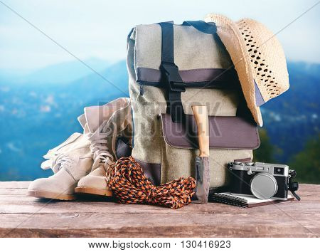 Tourism concept. Backpack, pair of boots and camera on blurred mountains background