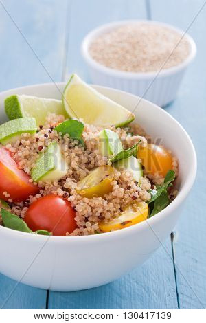 Quinoa, zucchini, tomatoes and spinach on blue wooden table