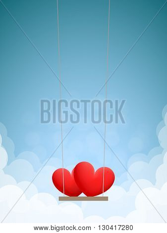Couple of red hearts on swing in the daytime sky with clouds