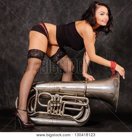 Young and beautiful fashion model posing in stockings and lingerie with tuba