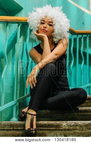 Girl in clown wig sitting on the stairs