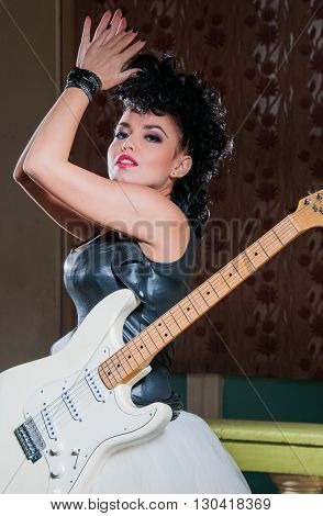 Photo of a female guitarist playing an electric guitar.