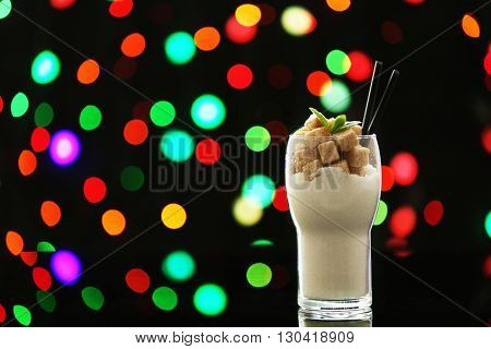 Glass with white granulated and brown lump sugar on dark bokeh background