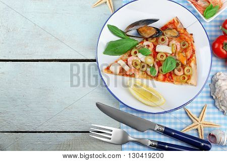 Pizza slices with seafood, red pepper and green olives on wooden table