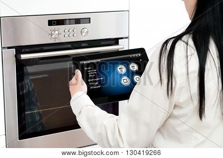 Woman sets up oven baking programme. Conception of using smart home application.
