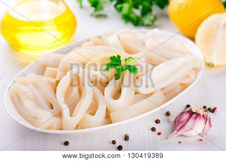 Raw Squid Rings On White Plate, Ready To Cook