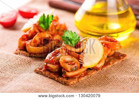 Appetizer With Spicy Tomato Squids And Lemon On Toast