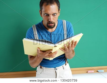 Astonished adult pupil looking in book with her mouth open. Photo of frightened student creative concept with Back to school theme