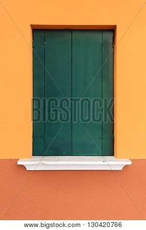 Picturesque old window with dark green shutters on orange wall (Burano island Venice Italy)