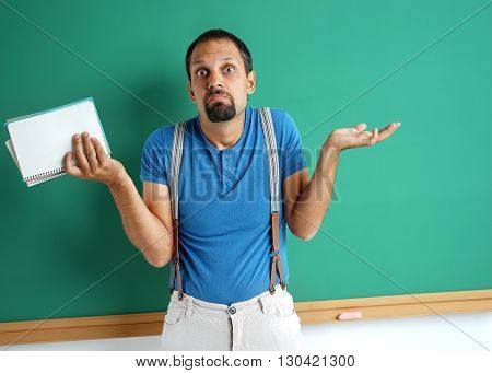 Doubting teacher spreads his hands looking at camera. Photo of adult man weighing decision near blackboard. Education concept