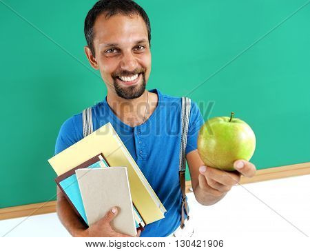 Smiling teacher hugging books and holding an apple. Creative concept with Back to school theme