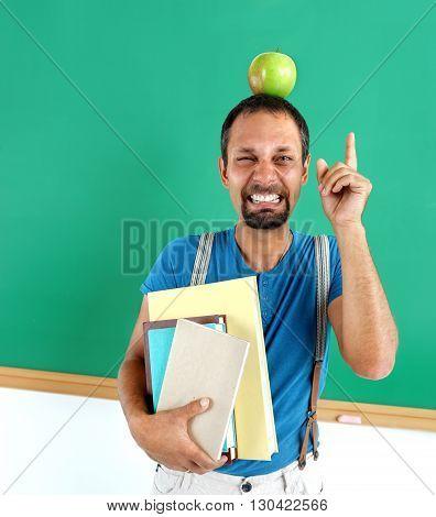 Amusing teacher literature with an apple on her head. Photo adult teacher near blackboard education concept