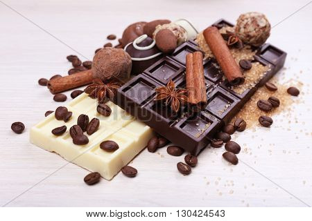 Spilled sugar and coffee beans with chocolates on wooden background