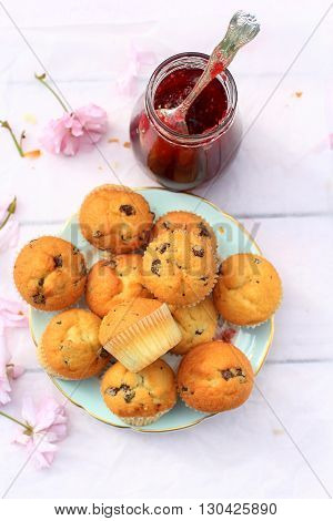 Rustic wooden breakfast background with fresh scones and blooming cherry flowers