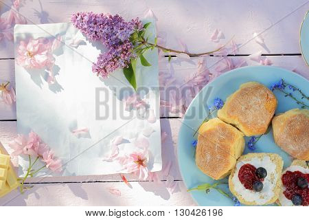 Beautiful spring breakfast background with Scottish scones lilac and cherry flowers