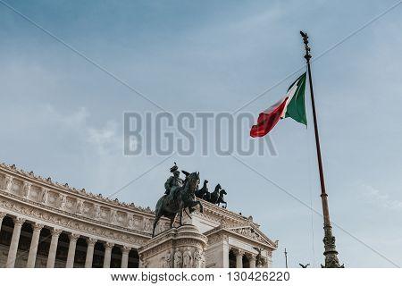 Il Vittoriano. Italian flag and blue sky background. Rome, Italy.
