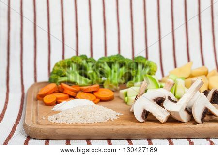 Fresh sliced soup ingredients laids on wooden cutting board. Side view low aperture shot