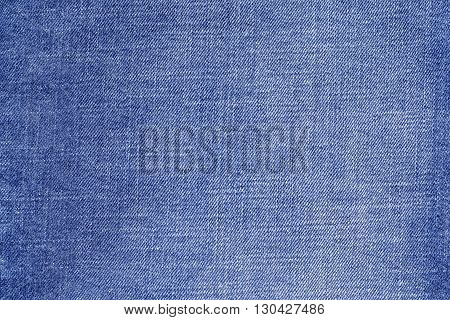 the textured background from rough cotton material or denim of pale blue color