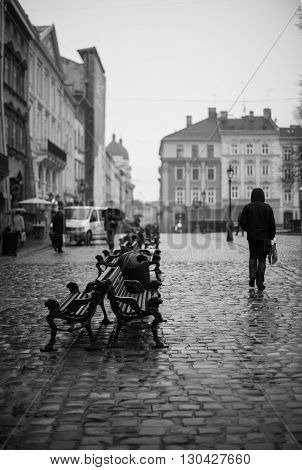 Lonely man silhouette walking on Lviv streets in autumn. Black and white shot, Lviv, Ukraine.