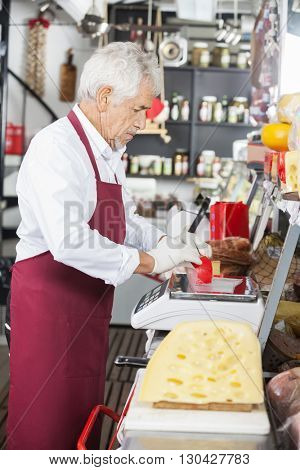 Salesman Wrapping Cheese At Counter In Shop