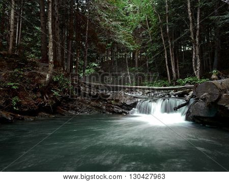 Cascade falls over mossy rocks in Carpathian mountains on autumn woods background.