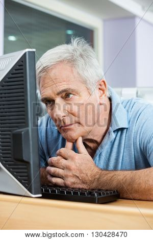 Tensed Senior Man Looking At Computer In Class