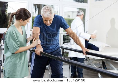 Female Physiotherapist Standing By Patient Walking Between Paral