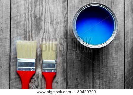 painting at home with open can of blue paint and two brush on wooden background top view