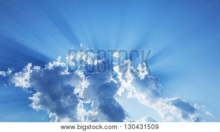 Sun slanting among from white clouds. Nature background.