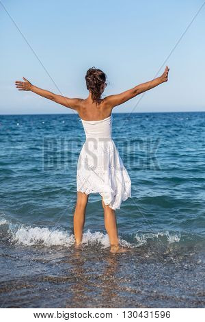 Happy woman stays in the sea water.