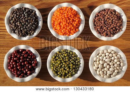 Colorful beans and lentils in ceramic bowls on a wooden background.