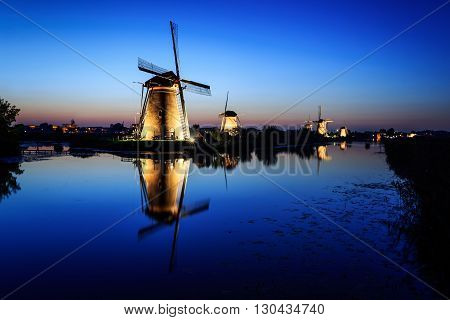 Historic illuminated windmills at the Dutch UNESCO World Heritage Site Kinderdijk with reflection in the water of the canal under a Blue Hour sky at dusk right after sunset in the beginning of the night in the Netherlands.