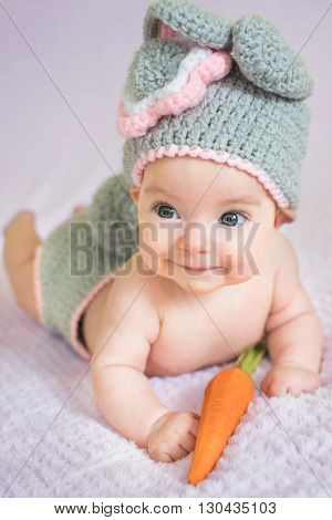 A baby with carrot in a bunny costume